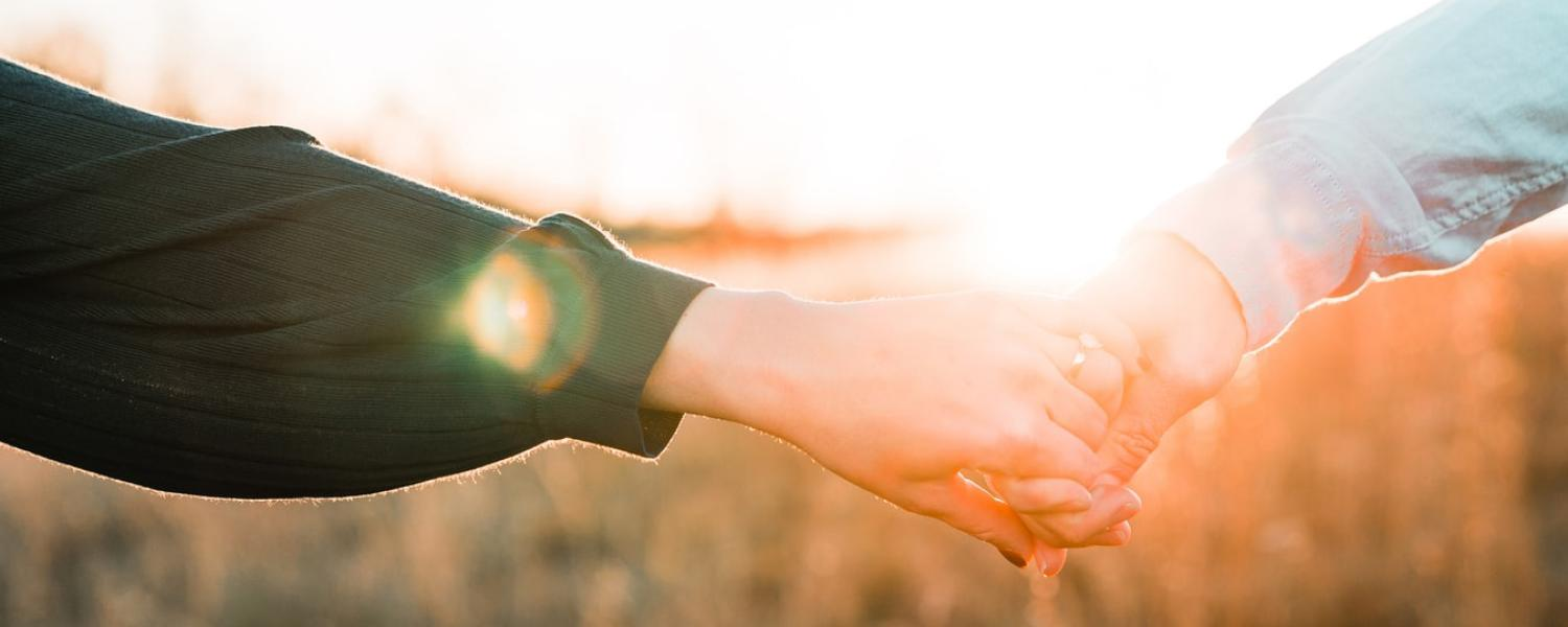Two people holding hands in front of sunset
