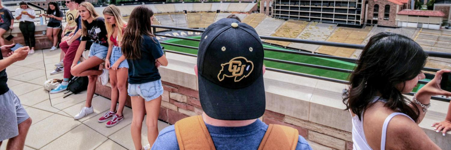Student with black CU Ralphie hat looks out over Folsom field observation deck at the flatirons.