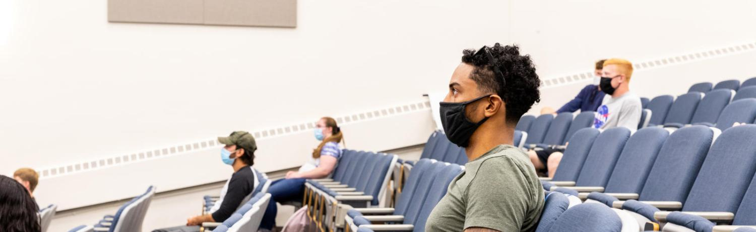 Students in masks sitting in a large lecture hall.