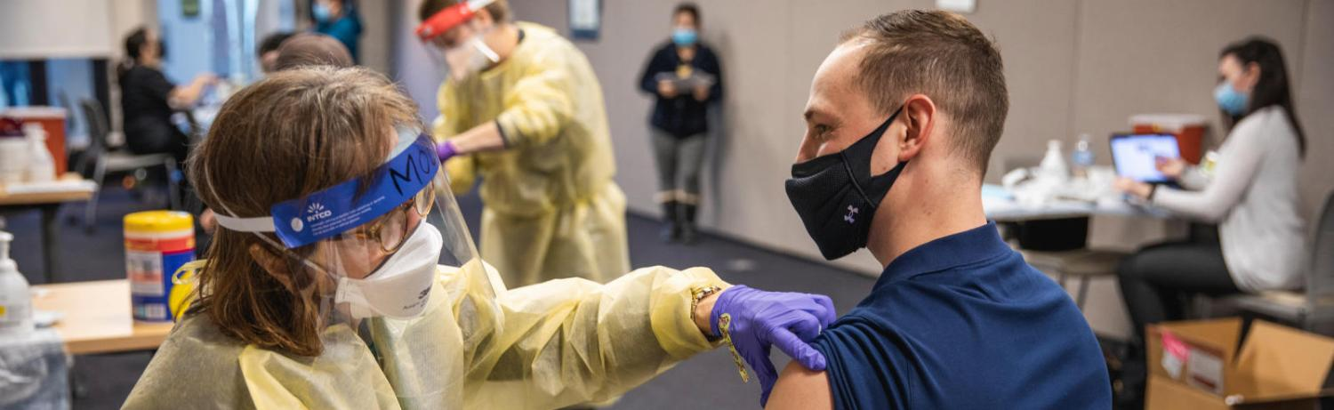 A nurse rolls up the sleeve of a masked man with short hair, preparing to give him a covid vaccine.