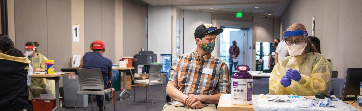 Man sitting at the COVID-19 vaccination clinic at CU Boulder.