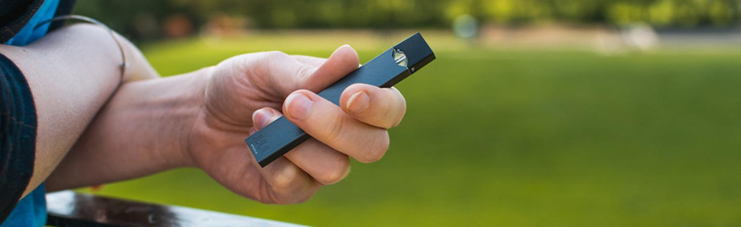 Person holding a vape pen outside in front of a grassy lawn.