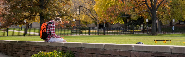 Student sitting alone on the brick wall near Farrand Field.