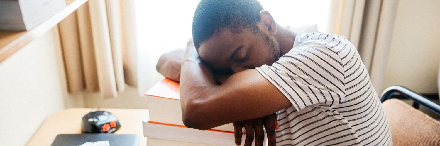 Student sleeping at his desk on a pile of textbooks.