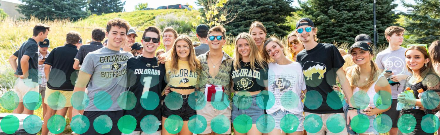 A large group of CU students poses together with their arms around each other outside on a sunny day.