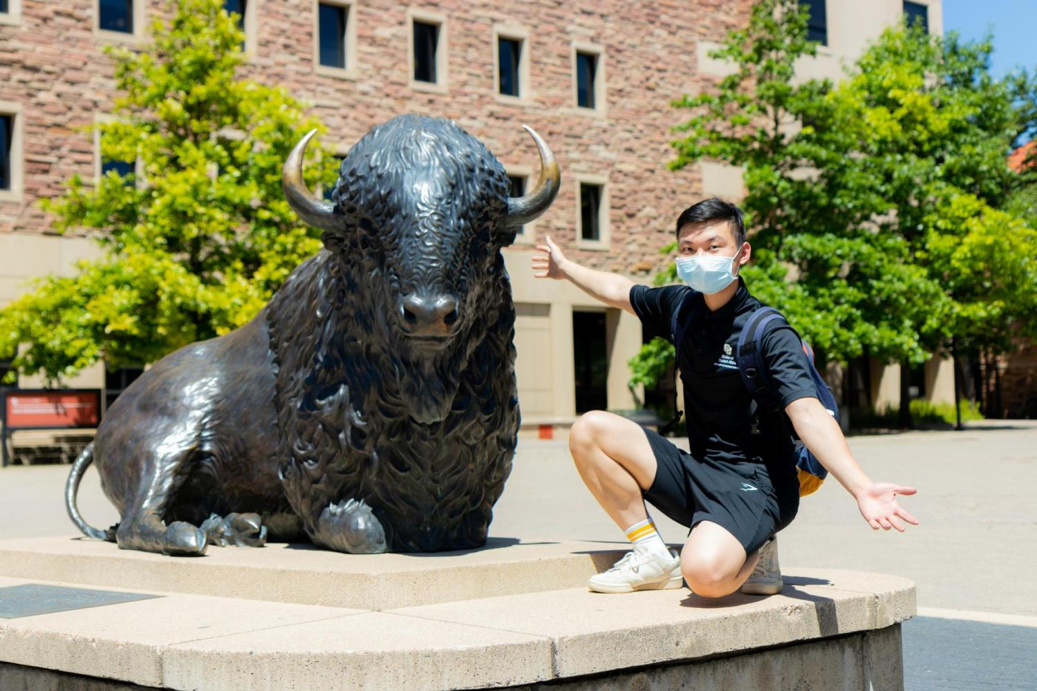 student in the sun posing next to a buffalo