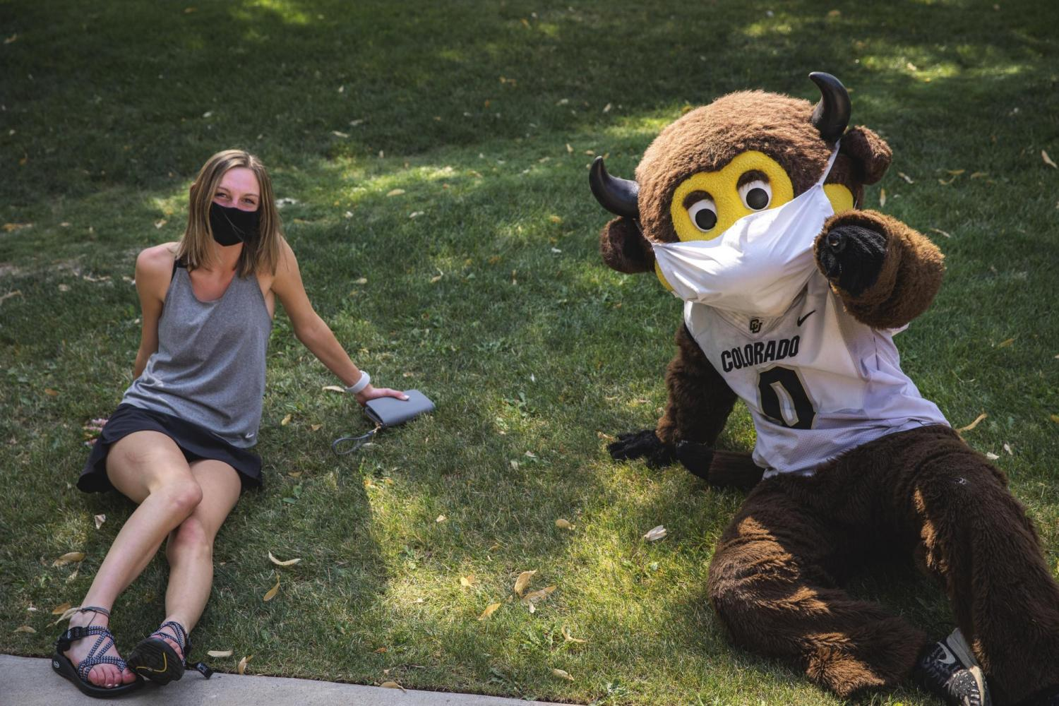 chip the mascot giving a peace sign with a student