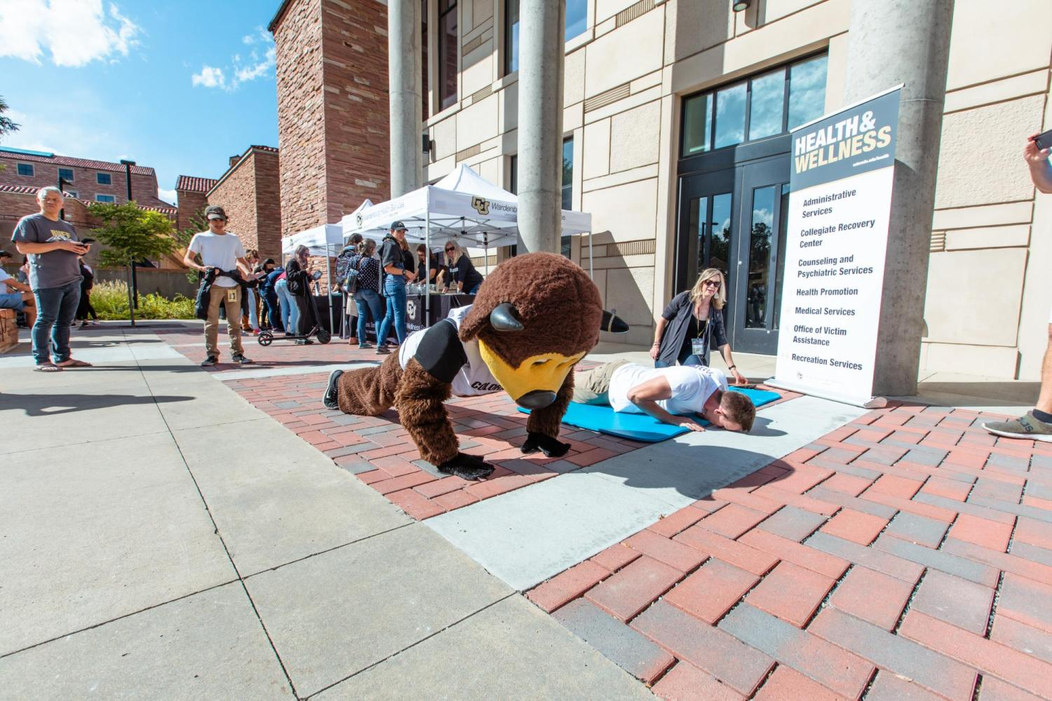 Chip doing pushups with a student