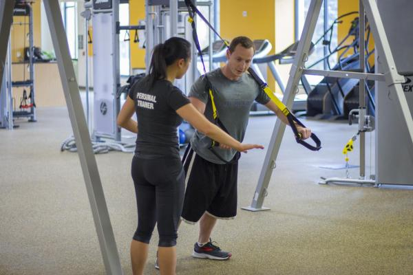 Personal trainer showing student how to use TRX