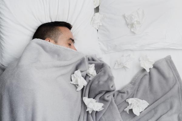 Male laying in bed covered in covers and used tissues