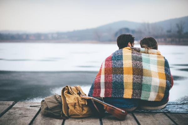 Couple sitting under blanket in the winter