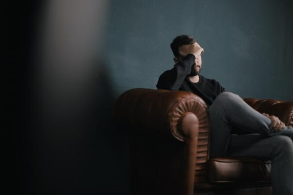 Person sitting on couch with head in hand
