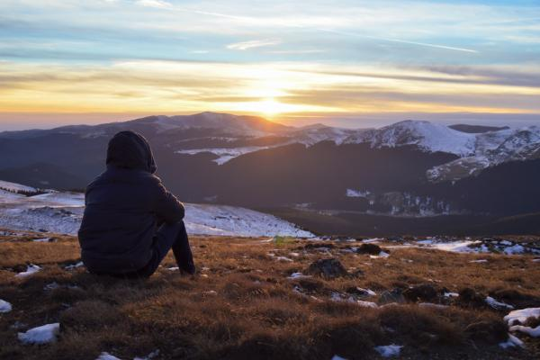 Person sitting alone at sunset on a mountain