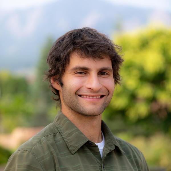 smiling man in a green shirt
