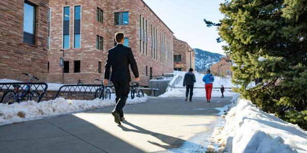 people walking through a snowy campus