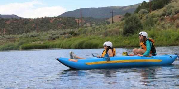 students rafting on the river