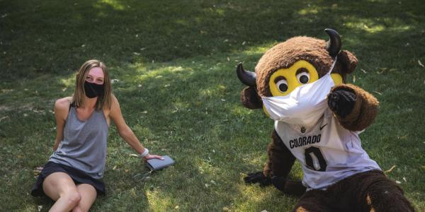 chip with a student on the grass wearing masks