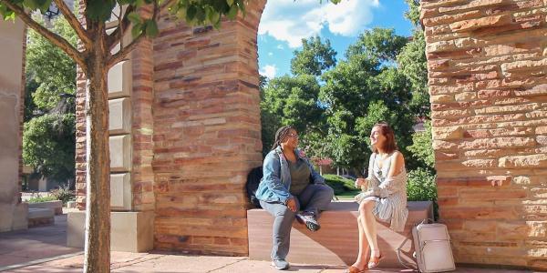 two women sitting under an arch talking