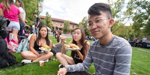 Students sitting outside eating at a university fair.