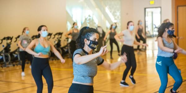 A group of students dances during a free fitness class at one of the rec center studios.
