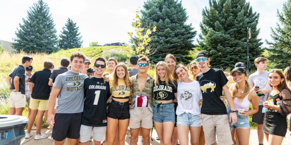 Students dressed in CU gear pose for a group photo together outside.