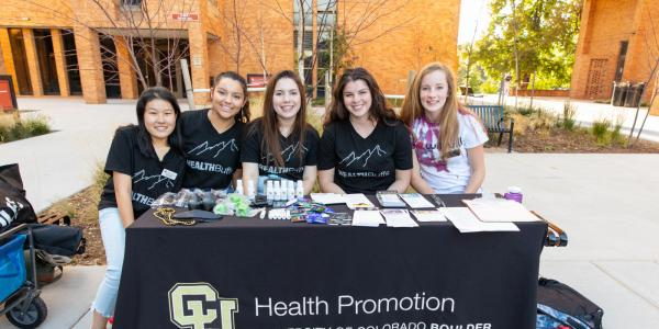 Health promotion students sitting at a booth at a campus event.