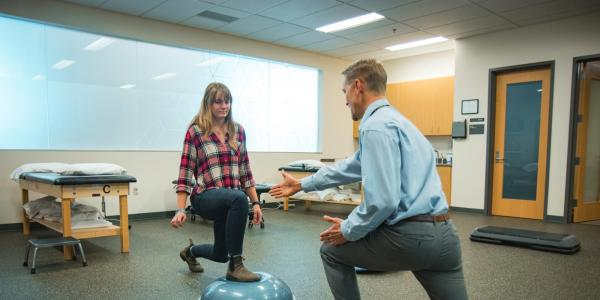 Physical therapist helping a student practice mobility on a physio ball.