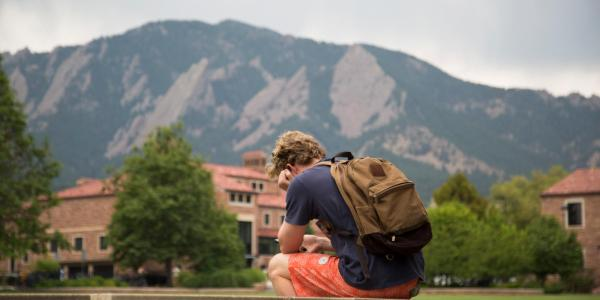 Student sitting on the ledge of Farrand Field looking at his phone.