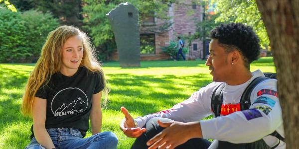 Student talking with a peer wellness coach outside on grass.