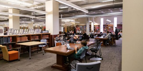 Students working on a group project at a table in the Norlin Library.