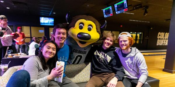 Four students sitting on a bench at The Connection bowling alley with Chip the Buffalo.
