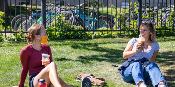 Two students sitting in the grass lawn drinking coffee together.