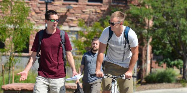 student walking alongside a bicyclist