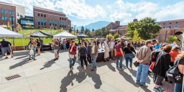 Students and families visit different booths at the Take Care Street Fair in front of the Visual Arts Complex on campus.