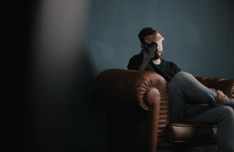 Man sitting in couch holding head