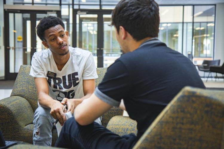 a peer wellness coach talking to a student