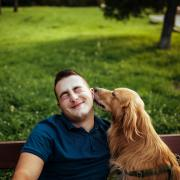 Man sitting on bench with his dog, licking his face