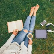 Person laying in the grass with headphones, a laptop and coffee