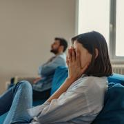 Girl sitting on the couch next to a guy with her hands over her face in frustration.