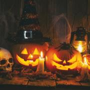3 jack-o-lanterns lined up in the dark with spooky candles and a skull ornament.