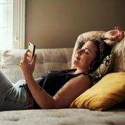 Student lying on the couch with headphones looking peacefully at her phone.