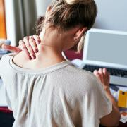 Girl rubbing her neck with discomfort while she works at a messy desk.