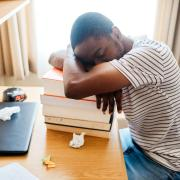 Student sleeping at his desk on a pile of textbooks