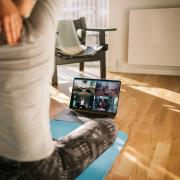 Woman sitting on yoga mat in front of live group chat video.