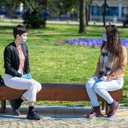 Two students in masks sitting on a bench talking to each other.