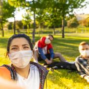 Girl taking a selfie wearing a mask in the park with her friends