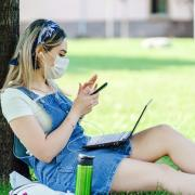 Female student in mask checking her phone outside while sitting under a tree.