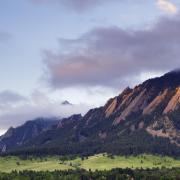 Photo of the flatirons at sunset with a foggy overcast.