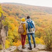 Two students bundled in sweaters standing on a hilltop overlooking colorful fall foliage.