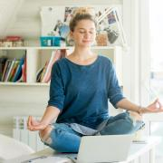 Girl meditating on her desk in her bedroom